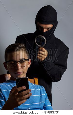 masked man spying data from smartphone of teen