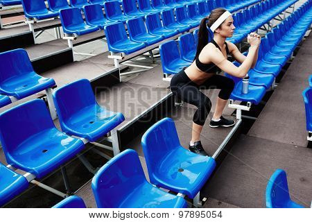 Pretty female doing physical exercise at stadium