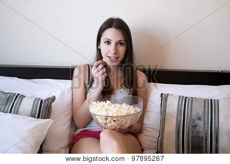 Young Woman In Bed Watching A Movie