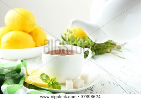 Pouring Tea Into Cup Of Tea On White Wooden Background