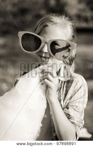 Happy teen girl eating cotton candy outdoor