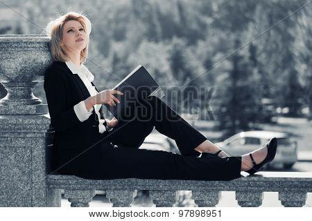 Young business woman with a folder sitting on the banister