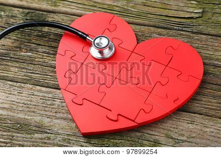 Red Puzzle Heart With Stethoscope On Wooden Background