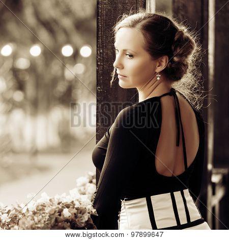 Sad beautiful fashion woman standing on the porch