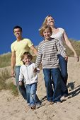 stock photo of holding hands  - A happy family of mother father and two sons walking holding hands and having fun in the sand dunes of a sunny beach - JPG