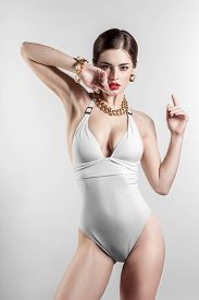 pic of monokini  - Sexy glamour model posing in white swimsuit on white background - JPG