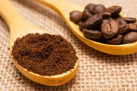 stock photo of coffee grounds  - Ground coffee and coffee beans on wooden spoon lying on jute canvas coffee grains - JPG