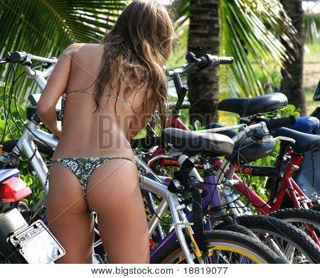 Girl on Ipanema beach picking up her bicycle