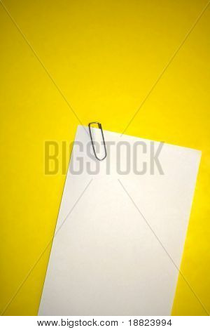 Memo paper with staple on yellow backgrund