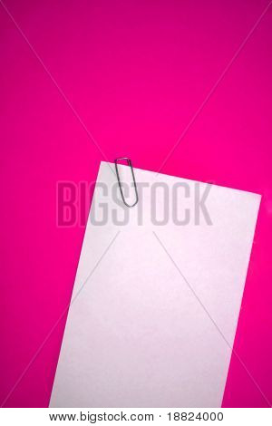Papel de Memo y grapa en backgrund rosa