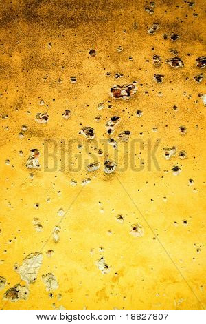 Pared amarilla con agujeros de bala