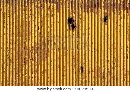 Rusty metallic background with shrapnel hole