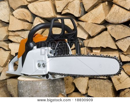 Chainsaw on stack woodpile background isolated