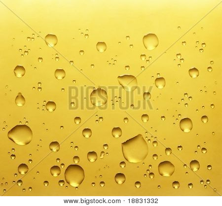 Real water drops on yellow background
