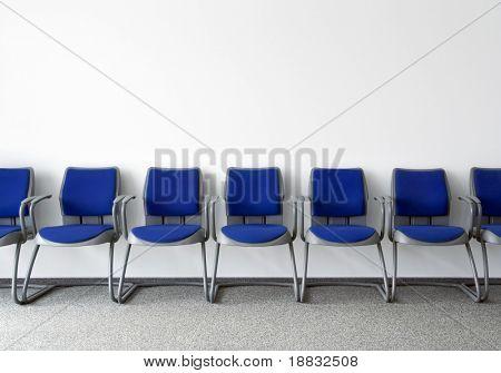 Blue chairs en sala de espera de vacío ordinario