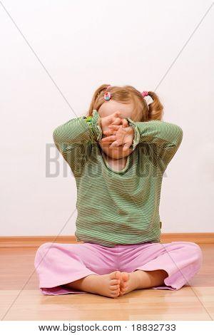 Kleines Mädchen versteckt sich hinter ihren Händen - traurig oder verspielt, mit Exemplar