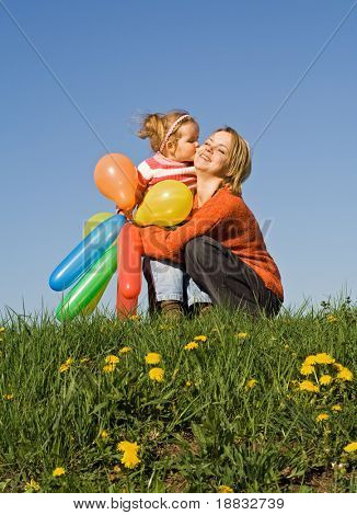 Cute girl with balloons kissing her mother on the early spring field