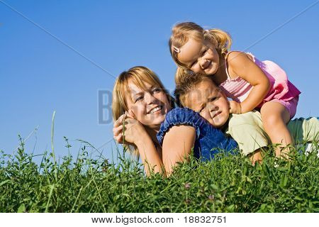 Smiling woman and kids in a heap laying on the grass outdoors