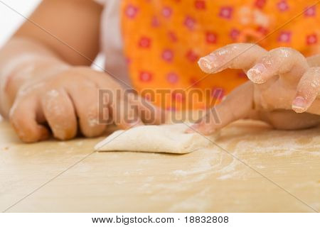 Little girl making cookies series - closing the edges around the filling, closeup