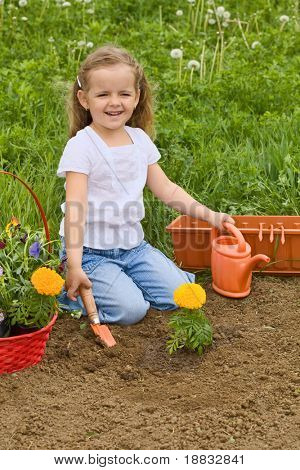 Little smiling girl gardening - planting flowers outdoors