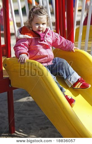 young girl on chute on outdoor playground