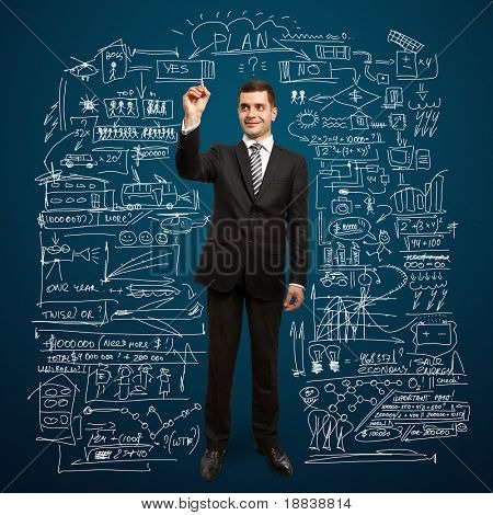 male businessman with marker writing something on glass write board