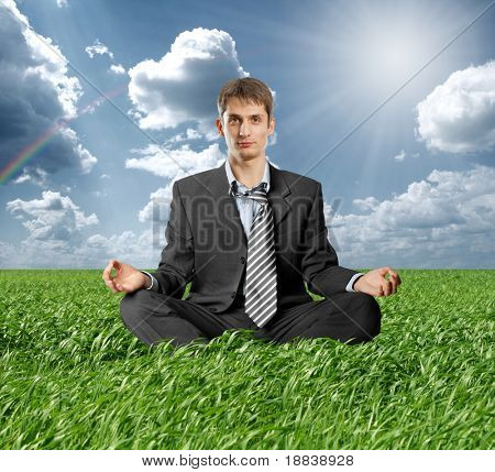 businessman in lotus pose meditating outdoors in grass