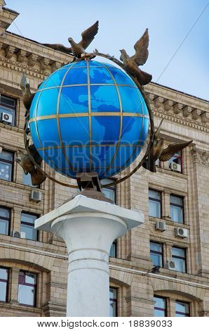 A statue of a blue terrestrial globe with doves of peace around it in Kiev, Independence square, Ukraine