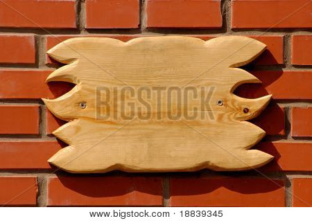 Empty wooden board sign on a brick wall texture background