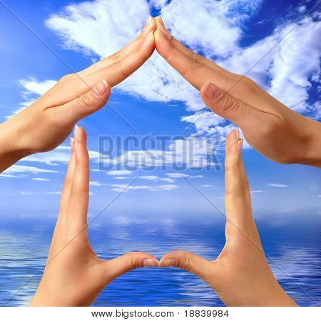 Female hands showing home sign over sky blue summer seascape background conceptual isolated with clipping path