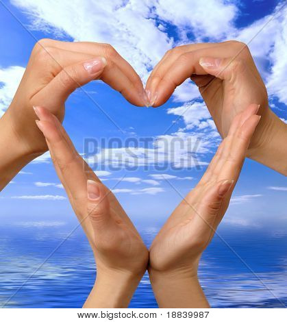 Conceptual heart symbol made from hands over blue seascape isolated with clipping path