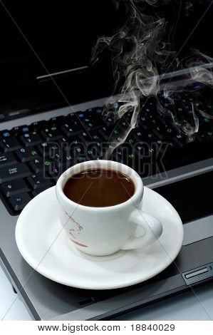 Cup of hot black steaming coffee on a laptop computer business office environment concept still-life background