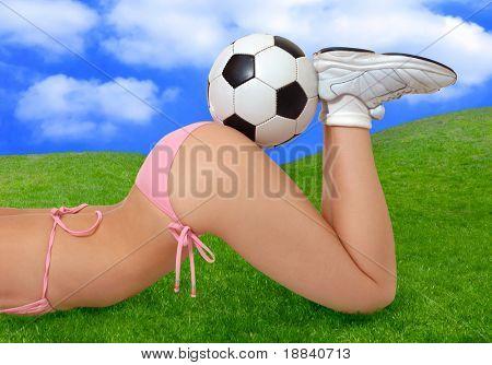 Sexy Mädchen im Bikini mit Fußball auf ihren Hintern auf grünen Sommer Gras liegend