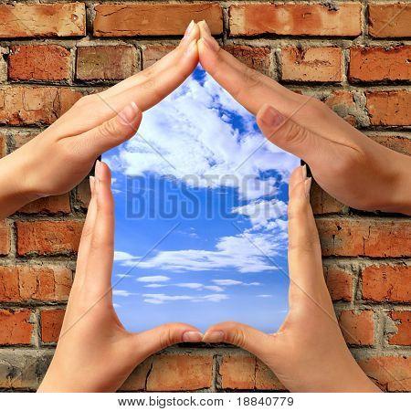 Casa símbolo feito de mãos sobre um tijolo com uma janela no céu azul conceitual Foto ilustração