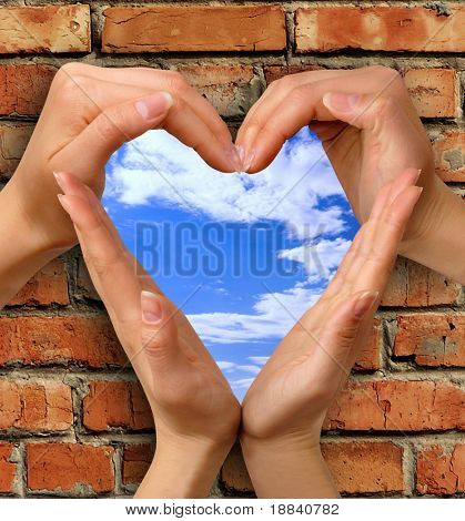 Heart symbol made from hands over a brick with a window into blue sky conceptual photo illustration