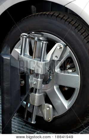 Car wheel fixed with computerized wheel alignment machine clamp
