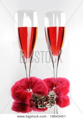 Two champagne flutes cuffed with red furry handcuffs romantic concept isolated on white background