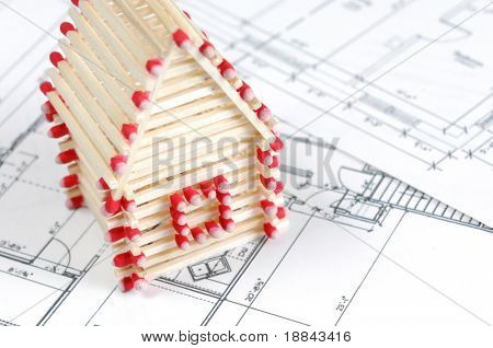 House made from matches standing on construction plans Construction industry Home renovation Real estate agency