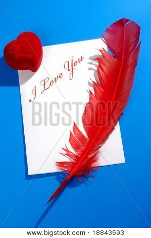 Valentines Day concept. Red heart-shaped jewelry gift box and a red quill on a letter with I love you written on it. Conceptual still life isolated on blue background