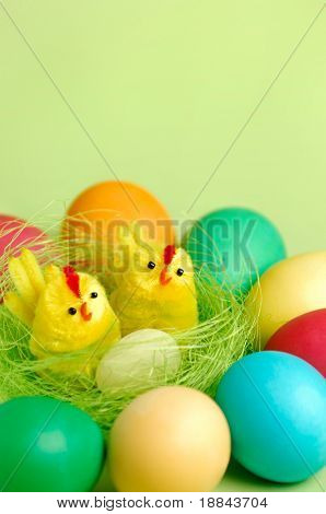 Colorful Easter eggs and two decorative chicks in a nest Artistic still life isolated on light green background