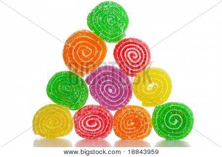 Coloridas frutas dulces cerca de dulces de azúcar sobre un fondo blanco