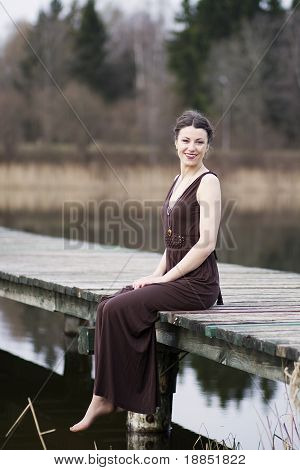 Young woman sitting on the footbridge