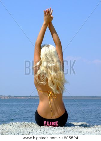 The Girl-Blonde Sits On Coast Of A Gulf, Having Lifted Hands Upwards