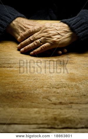 Old male hands on a table in a vertical composition