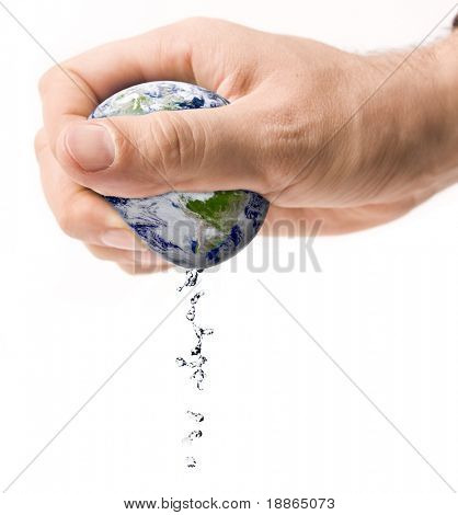 Hand squeezing earth with water drops isolated on white