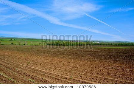 The ploughed field and the dark blue sky