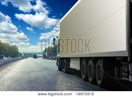 Weiße LKW auf der Asphaltstraße unter blauen Himmel mit Wolken