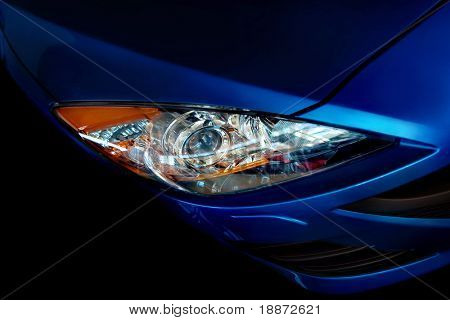 Part of the dark blue car on a black background