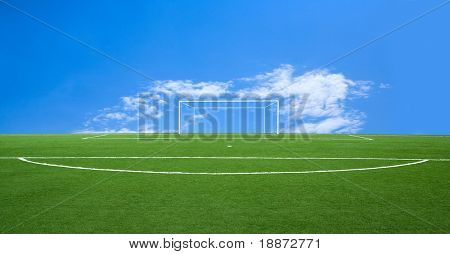 Green football ground against the sky
