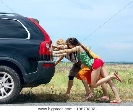 tres niñas empujar el coche roto